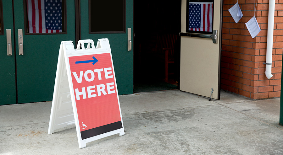 """Image of a polling place with a """"vote here"""" sign out front"""