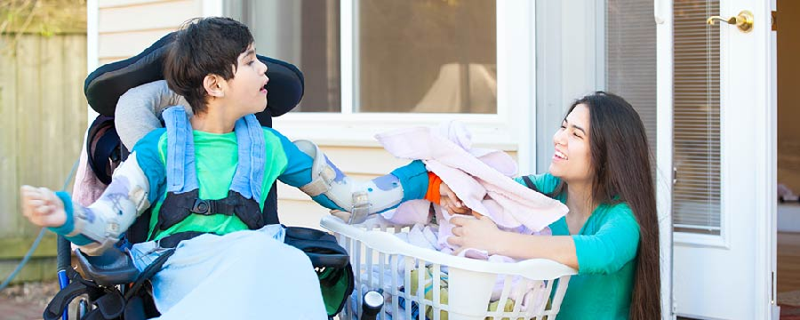 young boy with cerebral palsy in wheelchair assisting his mom with laundry in front yard