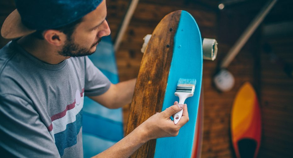 Photo of a man painting a skateboard.
