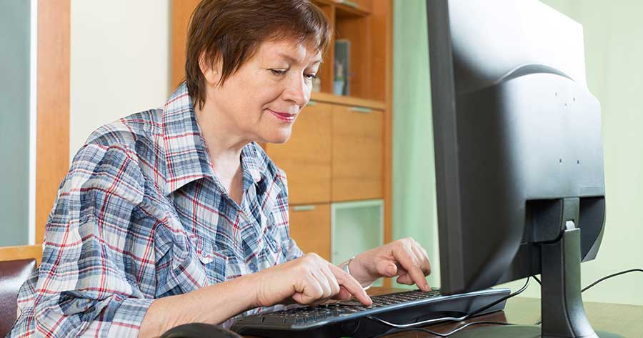 Elderly woman working at computer